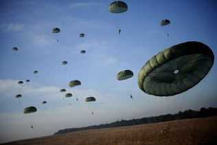 Army Soldiers from the 82nd Airborne Division from Fort Bragg, N.C., descend under parachute canopies to earn foreign jump wings Dec. 6 during Operation Toy Drop at Fort Bragg, N.C. Operation Toy Drop is an annual Airborne jump at Fort Bragg in its 11th year hosted by the Army Civil Affairs and Psychological Operations Command (Airborne), and supported by Fort Bragg's XVIII Airborne Corps and the Air Force Reserve Command's 440th Airlift Wing at Pope Air Force Base that gives Soldiers and Airmen the opportunity to help local families in need over the holidays while boosting morale and incorporating valuable training. More than 3,000 Soldiers donated a toy for a lottery ticket and the chance to jump under a foreign jumpmaster, earning them their foreign jump wings. This year, German and Irish jumpmasters will be issuing the commands from C-130 Hercules aircraft during the operation. (U.S. Air Force photo/Tech. Sgt. Jeremy Lock)
