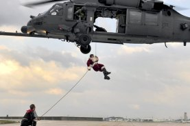 "Santa Claus, with an assist from one of his ""elves,"" rappels from an HH-60 Pave Hawk helicopter to greet children of the 31st and 33rd Rescue Squadrons at Kadena, Japan, Dec. 17, 2010. U.S. Air Force photo by Staff Sgt. Lakisha Croley"